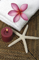 frangipani flower in towel with candle on burlap texture