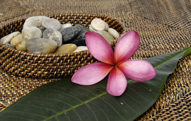 stones in wicker basket with flower with leaf bamboo mat