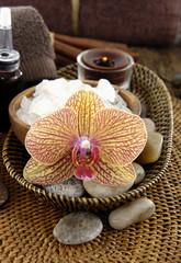 Spa aroma bowl of salt and orchid with towel with stones on mat