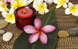frangipani with green leaf and candle with stones on burlap mat