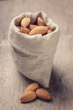 small sack bag full of almonds on wooden table