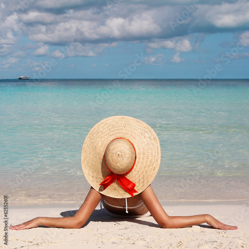 Vacation. Woman in Big Sun Hat tanning and relaxing on Beach