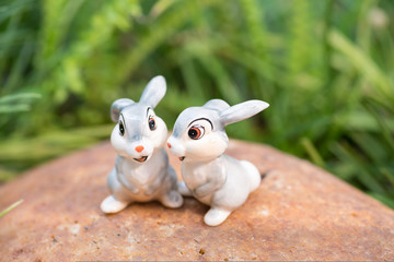Cute porcelain bunnies with green grass background