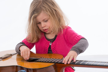 little girl is oplaying with a guitar