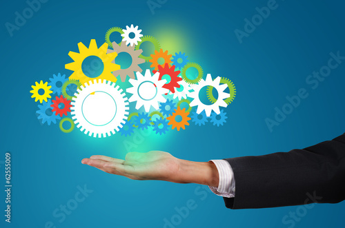 businessman holds up a cloud mechanism of gears, concept of read