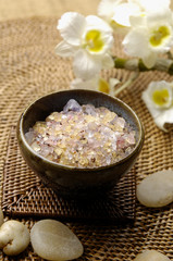 herbal salt in bowl and orchid with towel on burlap mat