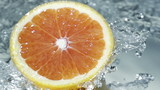 Halved grapefruit in running water