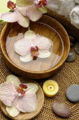 Orchid and water in bowl and candle with towel on burlap mat