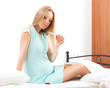 Cute pregnant woman sitting with thermometer on bed