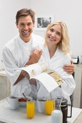 Happy young couple with recipe book in kitchen