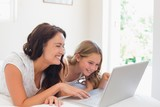 Woman with daughter using laptop in bed