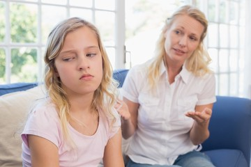 Angry mother explaining daughter on sofa