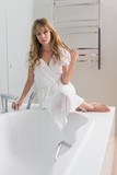 Woman sitting on the edge of bath tub in bathroom