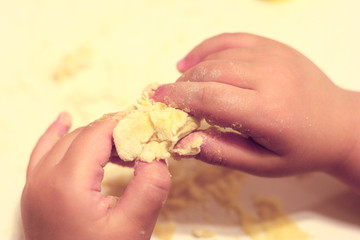 Child hands playing with dough