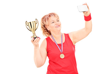 Woman in sportswear holding trophy and taking a selfie