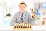 Senior chess player holding a trophy indoors