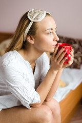 dreamy young woman with a sleepmask & cup of hot drink
