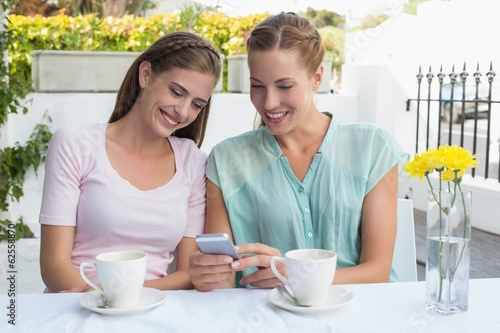 Female friends reading text message at coffee shop