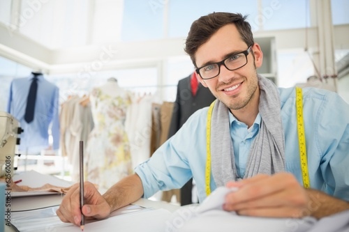 Smiling male fashion designer working on his designs