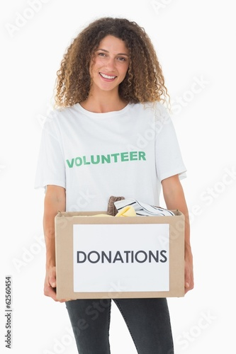Smiling volunteer holding a box of donations