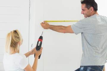 Rear view of a couple with drill and tape at new home