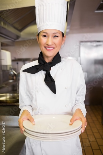 Smiling female cook holding empty plates in kitchen