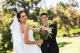 Happy newlywed couple with bouquet in park
