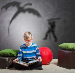 Preteen boy reading a story about a knight and a dragon