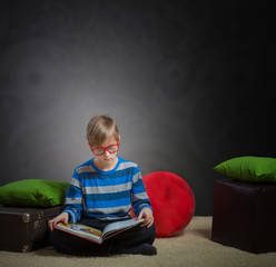 Preteen boy sitting on floor and reading book, dark background