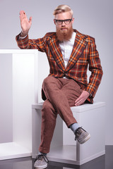 fashion bearded man smoking cigarette and waving his hand