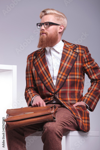 side of a fashion male model sitting holding his briefcase