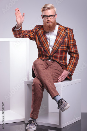 fashion bearded man smoking cigarette and waving his hand
