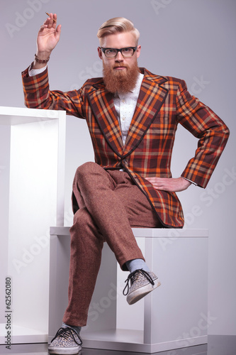 fashion man with long beard is sitting and smoking