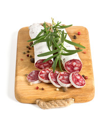 sliced salami with herbs on wooden cutting board