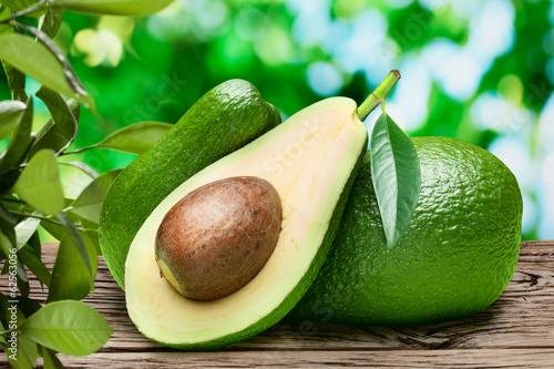 Avocado fruits on the old wooden table.