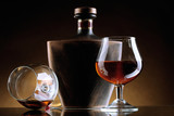 Glasses of brandy and bottle on brown background