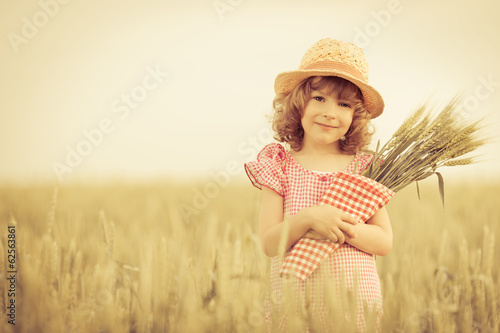 Happy child holding wheat