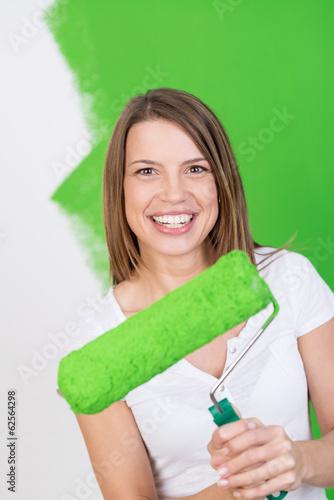 lachende frau streicht die wohnung grün