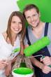 glückliches paar streicht die wohnung grün