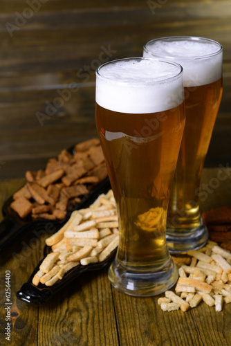 Glasses of beer with snack on table on wooden background