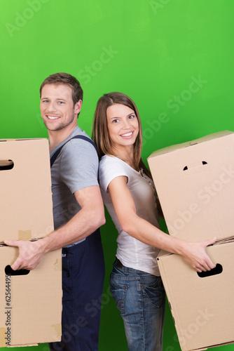 glückliches paar beim umzug vor grüner wand