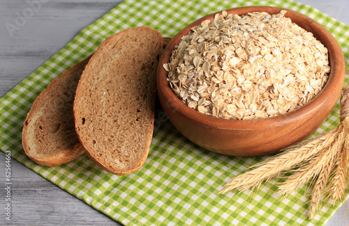 Composition with raw oat-flakes in bowl  and fresh bread