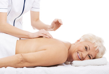 An old woman is having a massage.
