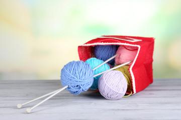 Woolen balls of yarn in rustic craft bag, om wooden table,