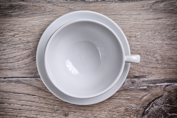 White porcelain cup with saucer on a wooden background