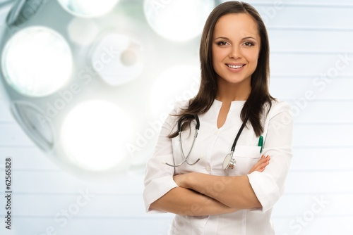 Young positive brunette doctor against lamp in surgery room