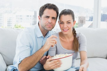 Couple watching movie on the sofa with bowl of popcorn