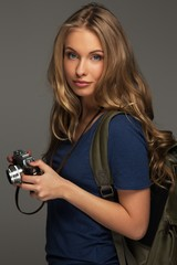 Positive young woman and blue eyes holding vintage style camera