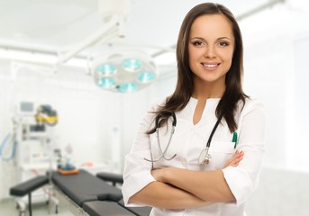 Young positive doctor woman in surgery room interior
