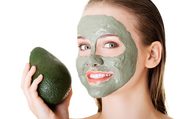 Spa woman in facial mask and avocado
